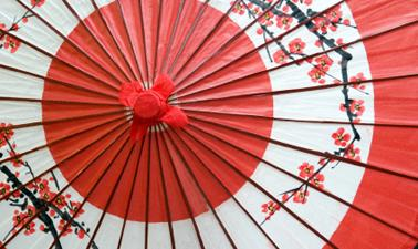 A close up shot of a red and white Japanese umbrella with a printed blossom pattern