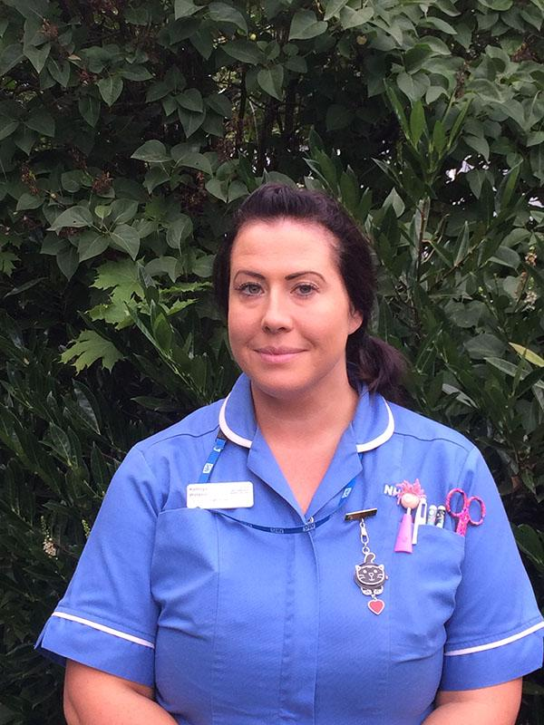 Kathryn Watson is wearing a nurse's uniform and standing against a green foliage background