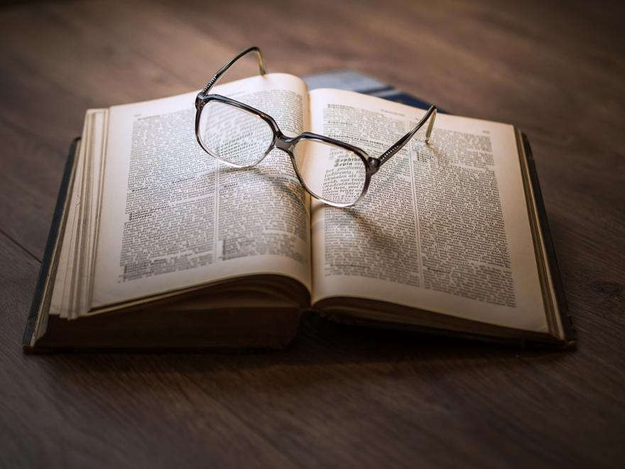 A pair of glasses sit atop of a large hardback book