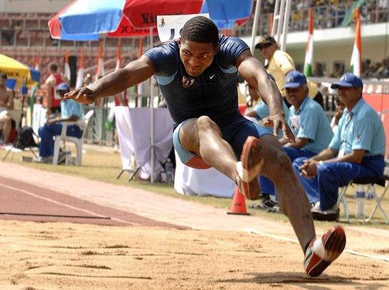 A man is landing in a sand pit during a long jump competition
