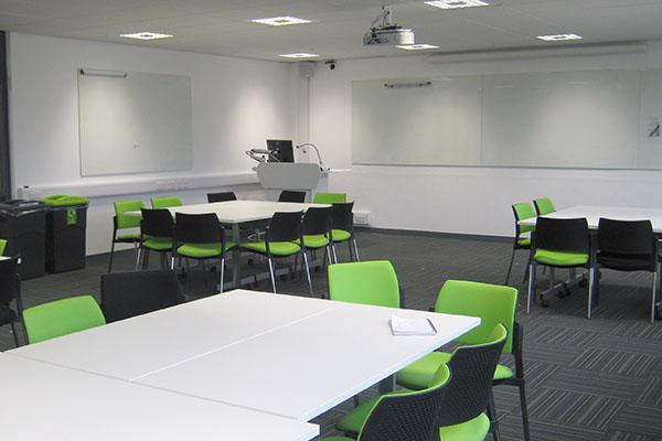 A lecture room with green chairs and white tables