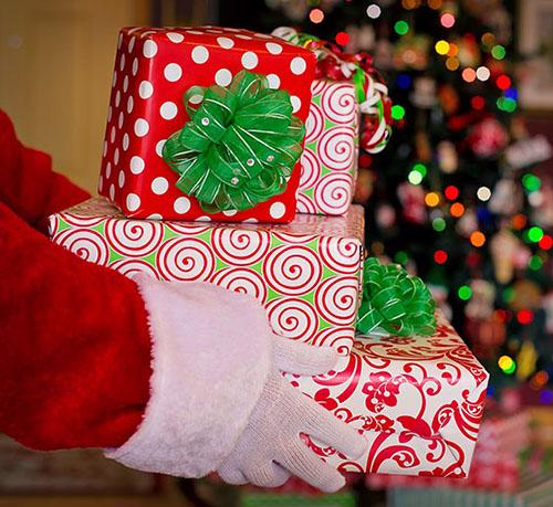 A close-up of Santa's hands holding a pile of wrapped presents