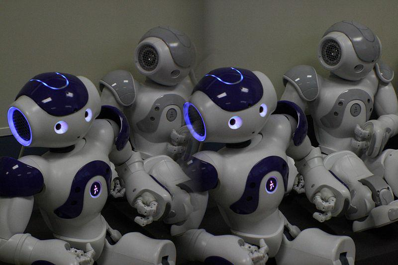 Several robots with glowing blue eyes sitting together