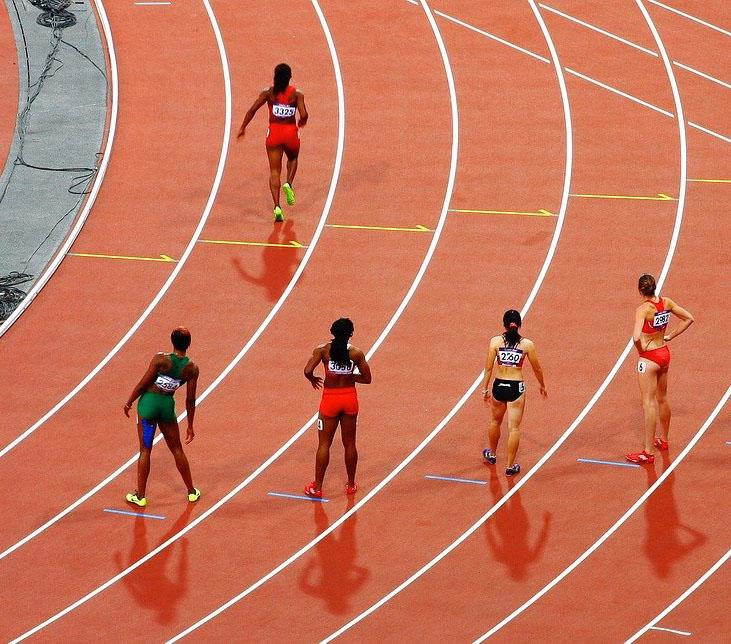 A group of runner dressed in brightly coloured lycra are standing on a running track