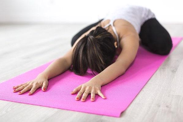 a lady is doing yoga on a pink mat