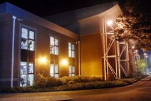 The outside of a sports centre lit up at night