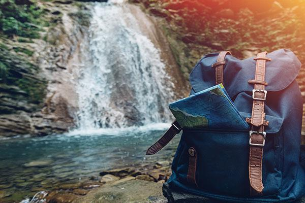 A backpack sits next to a waterfall