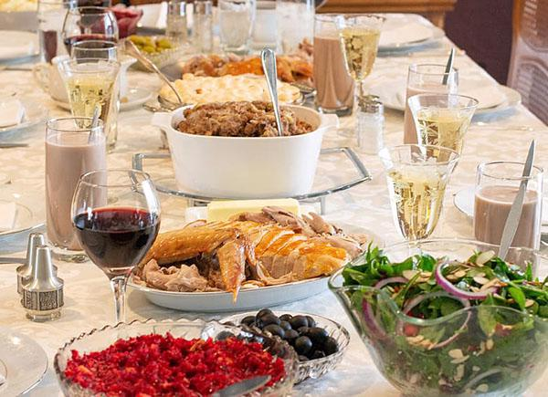 A table top is full of thanksgiving dinner including turkey, cranberry sauces and salads
