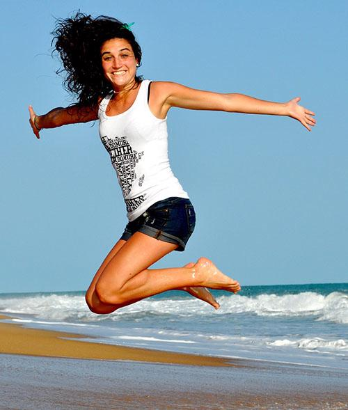 A woman on a beach is jumping and smiling