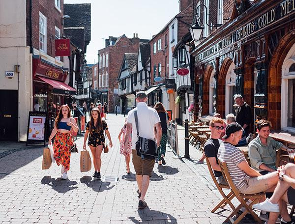 Several people are shopping and sitting outside cafes on a cobbled street in the sunshine