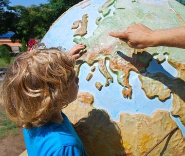 A child is pointing at Europe on a globe