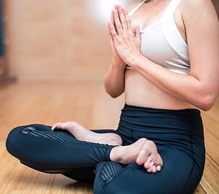A woman is sitting cross-legged in a yoga position