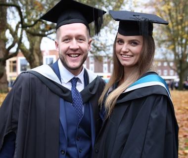 Male and female student in graduation robes