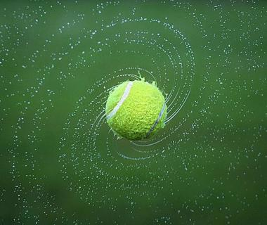 A close up shot of a tennis ball spinning
