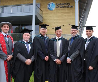 Group photo of mature men wearing graduation robes outside the university arena