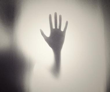 A ghostly hand is pressed against a window