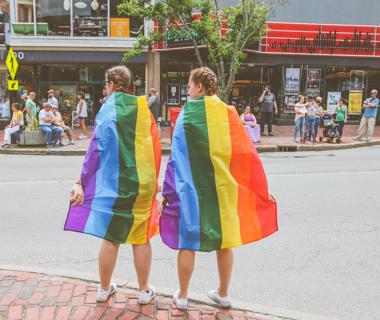 Two women are wearing the LGBTQ+ Pride Flag as capes