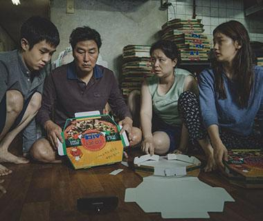 A shot from the film parasite of a family sitting around pizza boxes