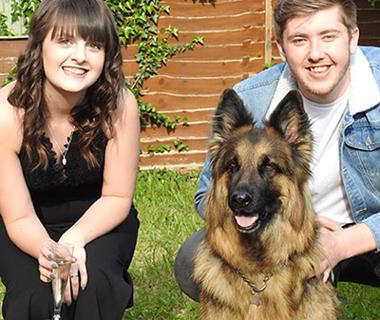 Young couple with a German shepherd in the foreground