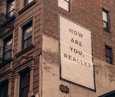 "We can see the side of a building which features a sign saying ""How are you really?"" on it"