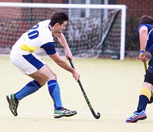 Man in a white top playing hockey