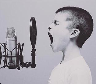 Young person yelling into a microphone