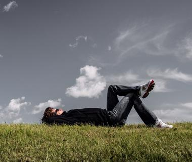 a man is lying on some grass staring up at the sky