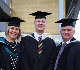 two mature students and a young man in graduation robes
