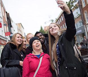 students in the high street taking a selfie