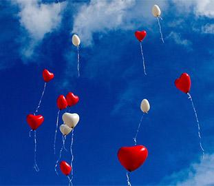 red and white heart-shaped balloons in a blue sky